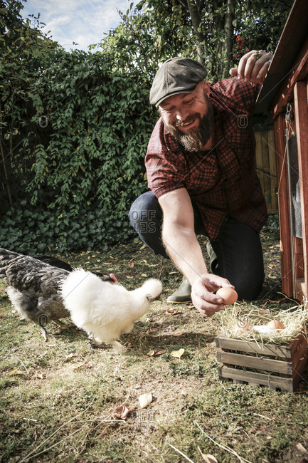 Man in his own garden- man holding egg of free range chickens