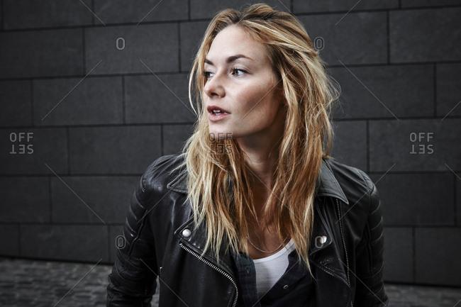 Confident young woman wearing biker jacket looking away
