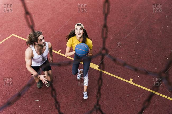 Young man and woman playing basketball on basketball ground