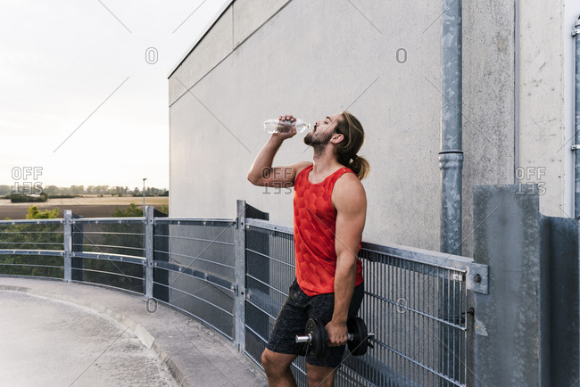 Young man drinking water after training with dumbbells