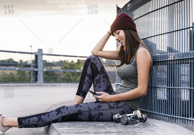 Young woman sitting on ground after dumbbell training- using smartphone