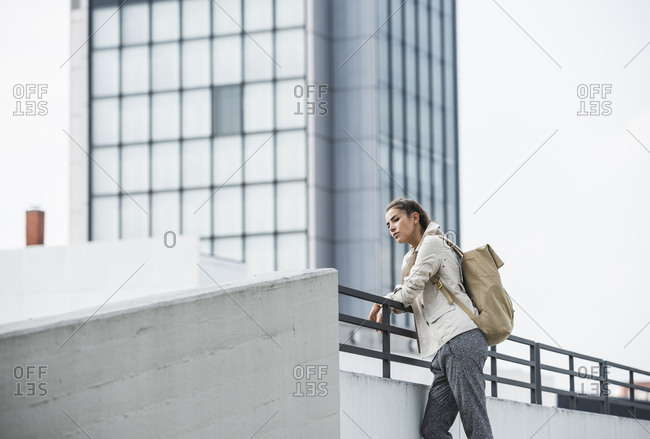 Young businesswoman leaning on railing- waiting in the city