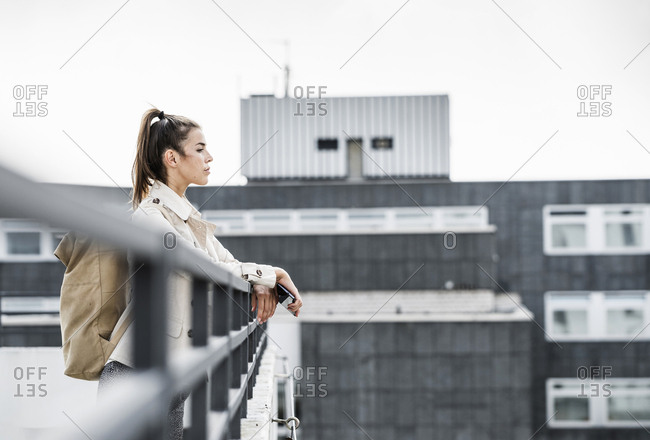Young businesswoman holding smartphone-  looking over
