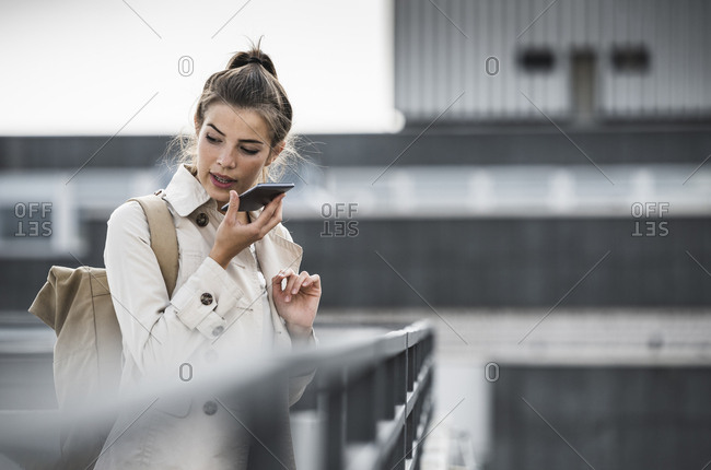 Young businesswoman using smartphone in he city