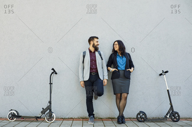 Smiling businessman and businesswoman with scooters leaning against a wall