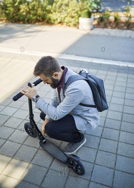 Businessman adjusting scooter