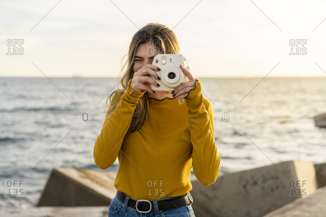Young beautiful happy woman taking instant photos by the sea