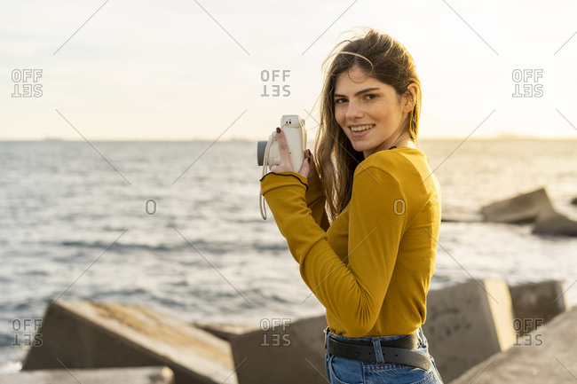 Beautiful happy young woman taking instant photos by the sea