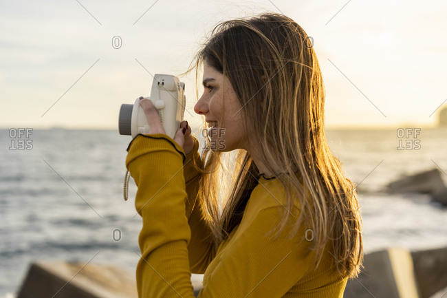 Side view of young beautiful happy woman taking instant photos by the sea