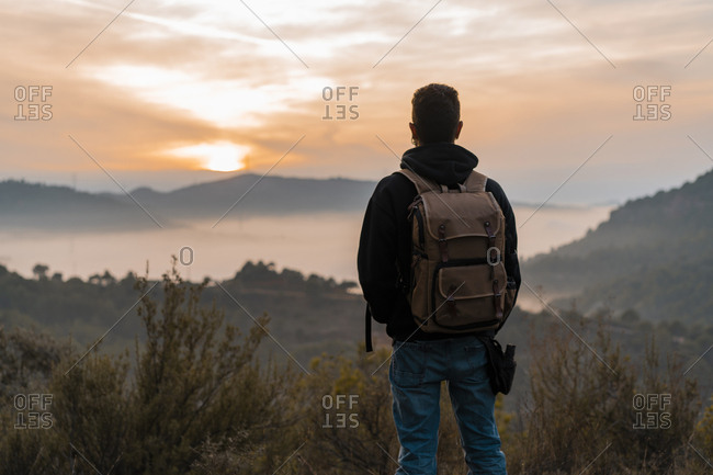 Rear view of man with a backpack looking at the sunset from a hill