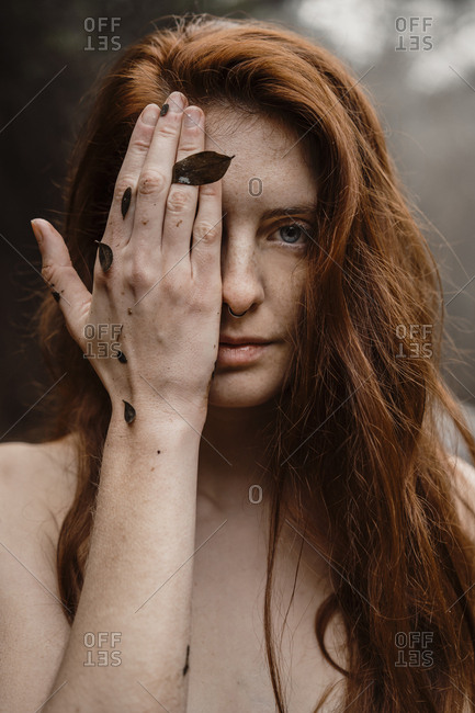 Portrait of ginger young beautiful woman covering eye with hand