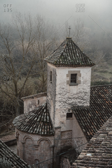 Old church in small village in foggy forest