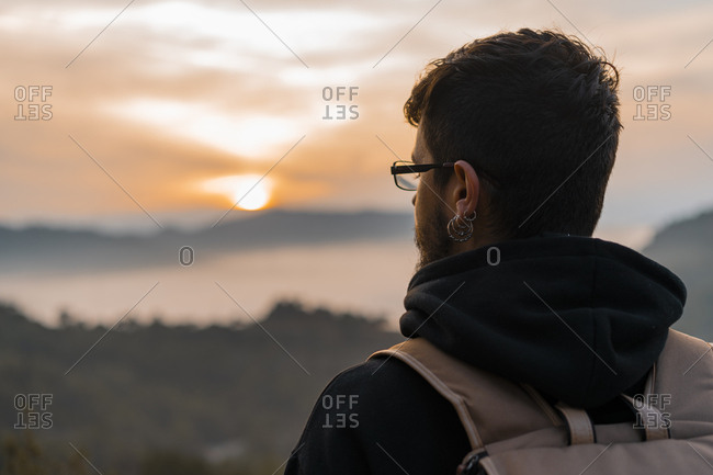 Rear view of a man with a backpack looking at the sunset from a hill