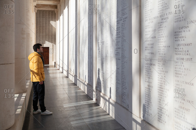 Ypres, Belgium - February 12, 2018: Man viewing wall of names of soldiers missing from the First World War inscribed on the Menin Gate memorial to the missing