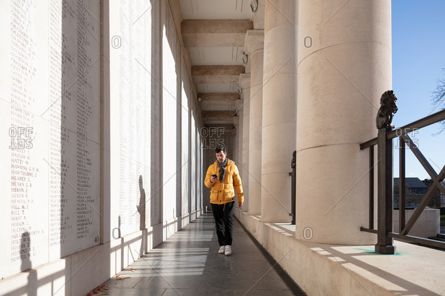 Ypres, Belgium - February 12, 2018: Man at the Menin Gate memorial to the missing using cell phone