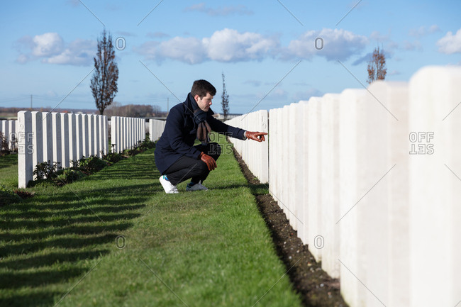 Man visiting grave of fallen soldier on Veteran's Day