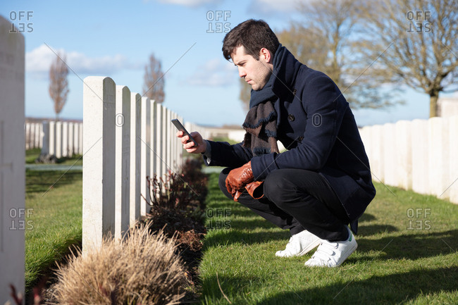 Zonnebeke, Belgium - February 12, 2018: Man looking up information on mobile phone about soldier grave at military cemetery
