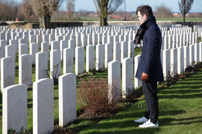 Zonnebeke, Belgium - February 12, 2018: Young man overlooking the graves on a military cemetery for Veterans