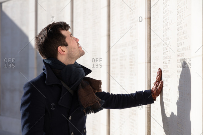Zonnebeke, Belgium - February 12, 2018: Man touching the Memorial wall at Tyne Cot Cemetery