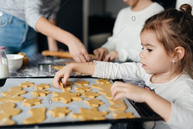 Cute little four year old girl helping mom to make gingerbread cookies