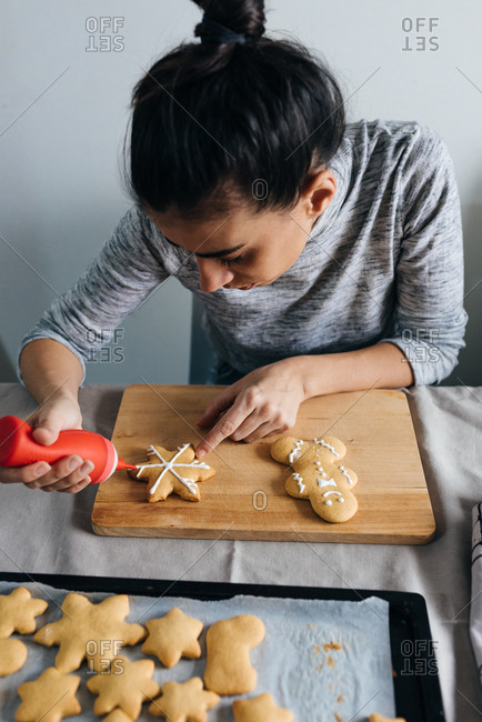 Person decorating gingerbread cookies with white icing