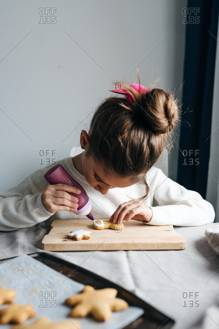 Girl decorating gingerbread cookie with white icing