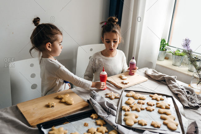 Two small girls decorating gingerbread cookies
