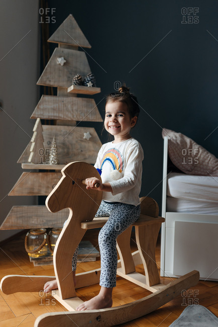 Girl sitting on her wooden horse in front of the wooden Christmas tree
