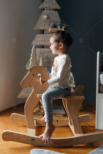 Side view of girl sitting on her wooden horse in front of a wooden Christmas tree