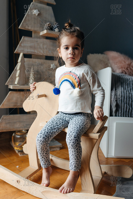 Little girl sitting on a wooden horse in front of a wooden Christmas tree