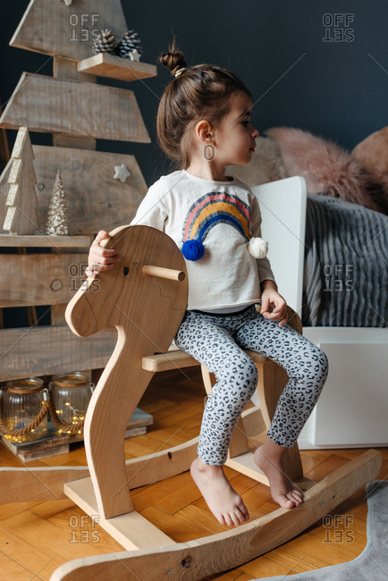 Little girl sitting on her wooden horse in front of a wooden Christmas tree