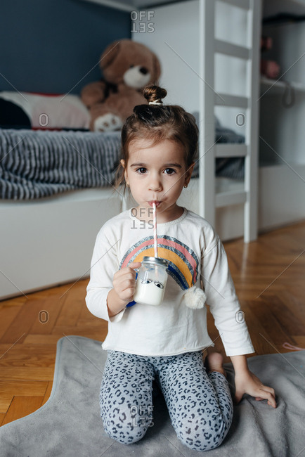 Cute four year old girl drinking milk from a jar with a straw