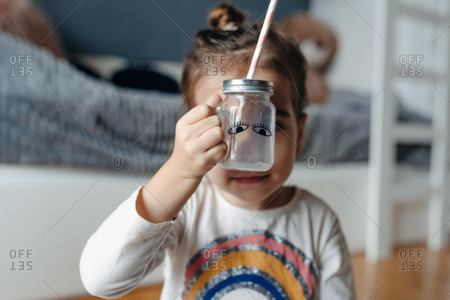 Cute four year old girl holding empty milk jar in front of her face