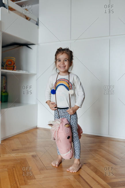 Cute four year old girl playing with her cloth riding horse
