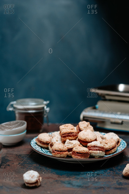 Homemade macaron cookies on a plate on dark background