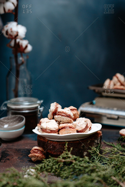 Homemade holiday macaron cookies on a plate on dark background