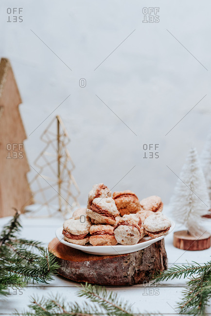 Homemade macaron cookies by Christmas tree on light background