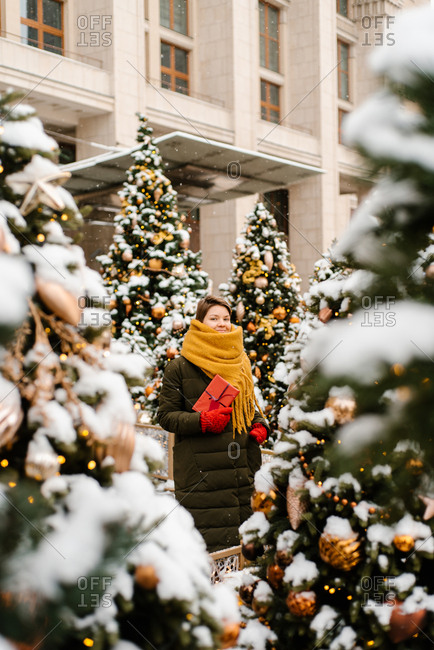 Woman outdoor surrounded by snowy Christmas trees