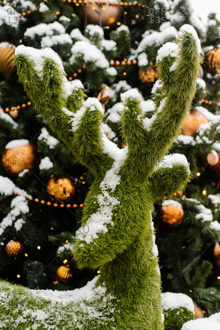 Snowy Christmas tree and green reindeer decoration