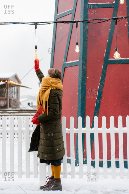 Woman outdoor looking hanging lights in the snow