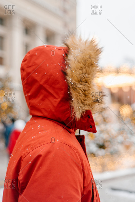 Man outside wearing red jacket with furry hood in the snow