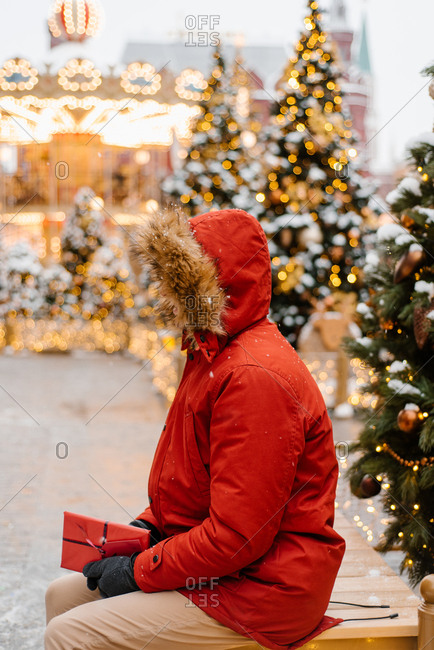 Man in red jacket sitting by an outdoor Christmas tree in the snow