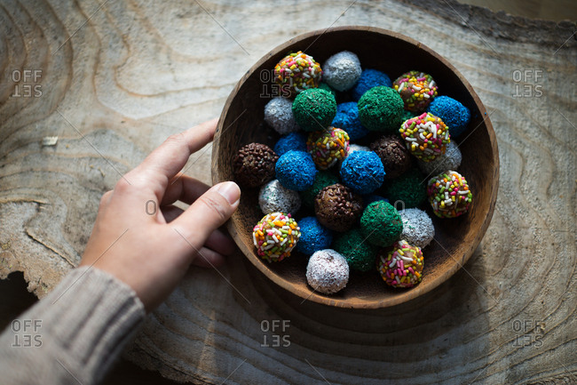 Hand and bowl of colorful cookie balls