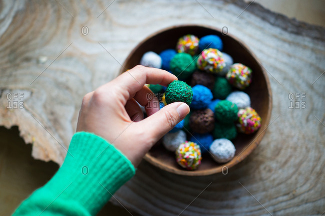 Hand holding round colorful cookie ball