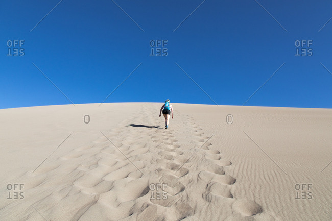 Low angle view of woman walking at Great Sand Dunes National Park and Preserve
