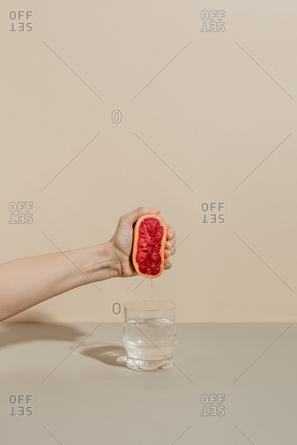 Hand is squeezing grapefruit