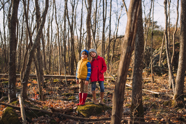 Two young kids playing in the woods in the late fall