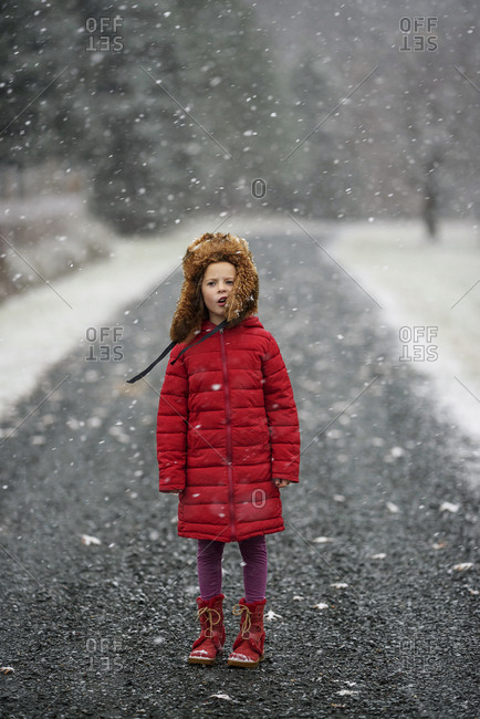 Young girl playing in falling snow