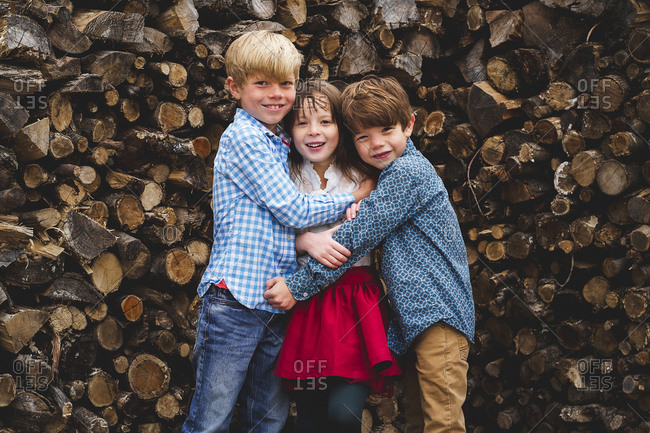 Portrait of three kids dressed up hugging each other