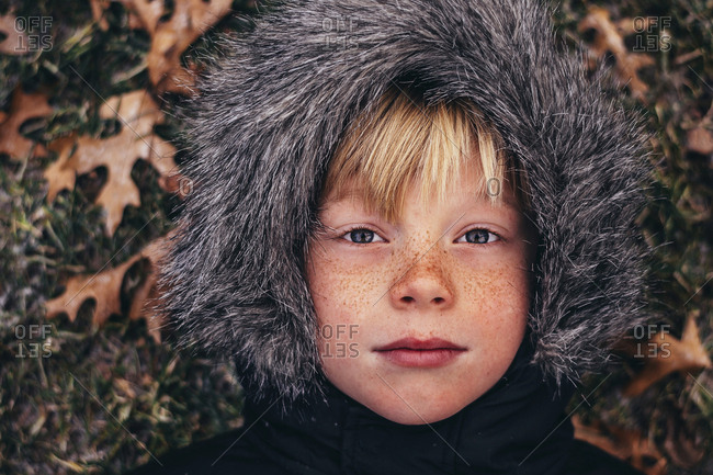 Overhead portrait of young boy in furry hood